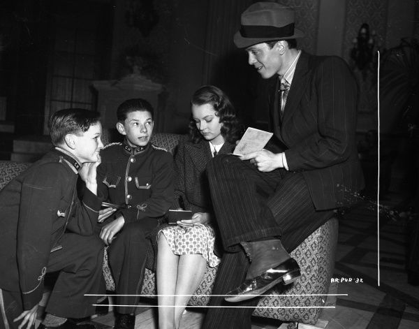Carol Marsh and Richard Attenborough signs autographs for two young extras dressed as bell boys