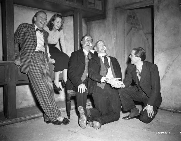William Hartnell, Carol Marsh, Wylie Watson and Richard Attenborough smile with the dummy prop used for the sequence of the killing of Watson's character, Spicer