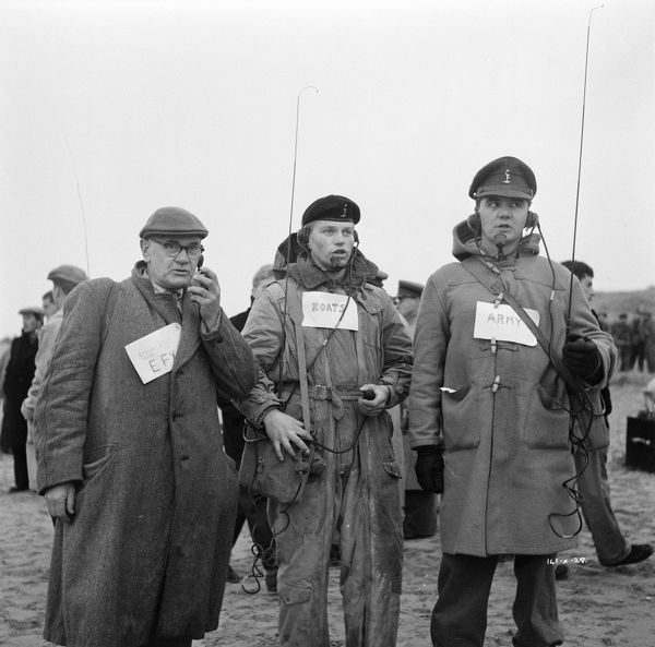 Members of the production team with labels to indicate to the extras who they are directing