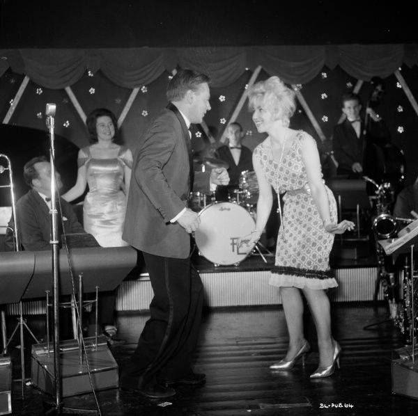 Gwendolyn Watts as Rita dances on stage during the Dance Hall scene of Billy Liar, in the background singer Muriel Day