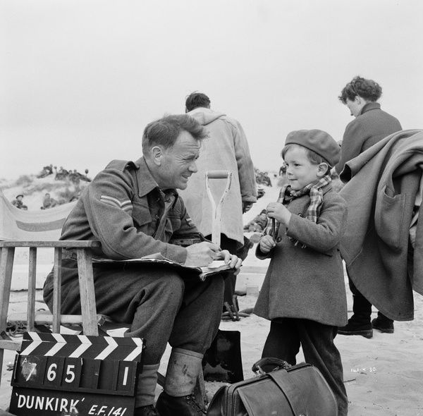 John Mills on the set of Dunkirk in a pause from filming with large clapperboard by his chair