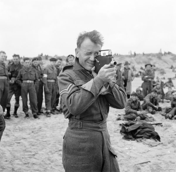 John Mills with a small film camera in front of extras on the set of Leslie Norman's Dunkirk