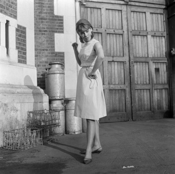 Julie Christie smiles in a summer dress in a portrait taken outside Wormwood Scrubs during the filming of Billy Liar