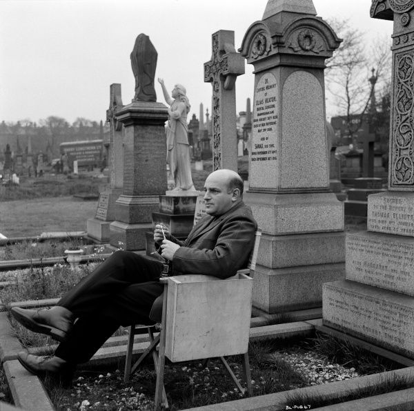 John Schlesinger sits on a chair in Undercliffe cemetery,Bradford, during the filming of his film Billy Liar in 1963