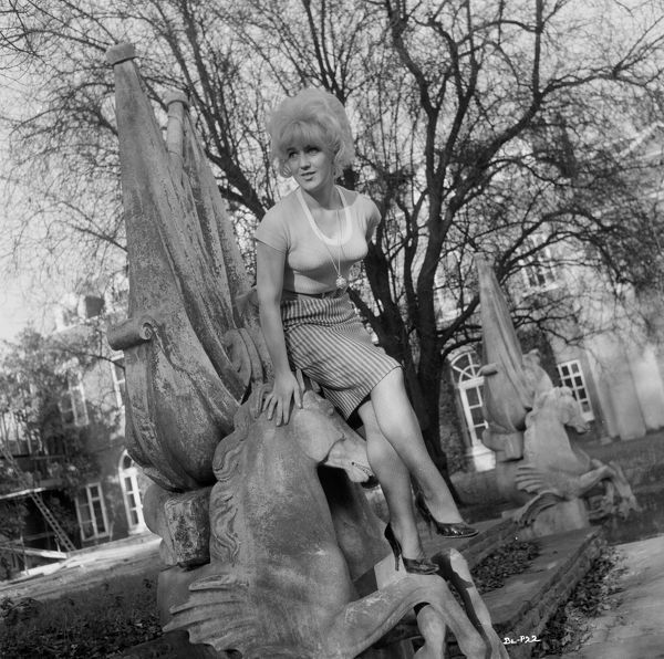 Gwendolyn Watts (Rita) poses on an ornate sculpture for a portrait to promote the release of Billy Liar in 1963