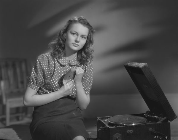 Carol Marsh as Rose listens to a record in a promotional portrait for the release of John Boulting's thriller based on Graham Greene's novel