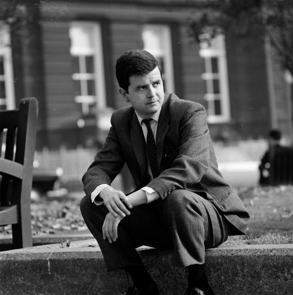 Rodney Bewes sits by the side of a park during the filming of John Schlesinger's Billy Liar (1963)