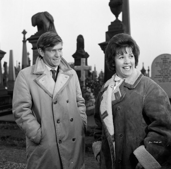 Actors Tom Courtenay and Helen Fraser smile on the cemetery set of Billy Liar (1963)
