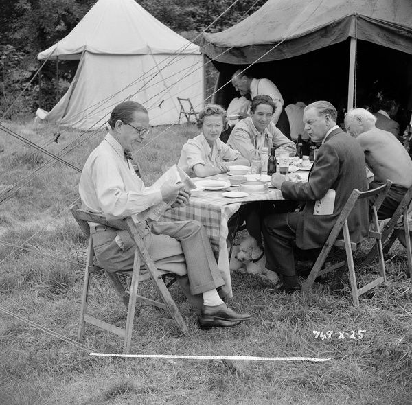 Stanley Holloway reads the newspaper with Gabrielle Brune, Naunton Wayne and John Gregson looking sitting at a picnic table