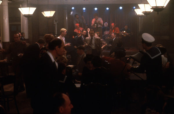 A jazz sextet plays in the background of a busy club scene taken from Fred Schepisi's Plenty (1985)