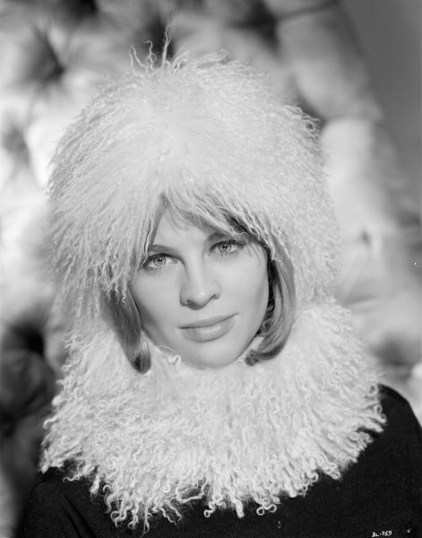 Julie Christie smiles and wears a boa feathers hat in a publicity portrait for the release in the UK of Billy Liar (1963)