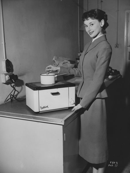 Audrey Herburn poses as Eve Lester with a Belling cooker in a portrait taken for the promotion of ABPC's Young Wives Tale released in 1951
