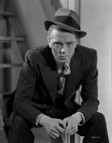 Richard Attenborough as Pinkie seated and moody wearing a hat