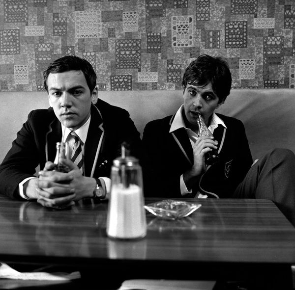 Terry (Robert Lindsay) and Jim (David Essex) in a cafe in their school uniform in the first part of the film