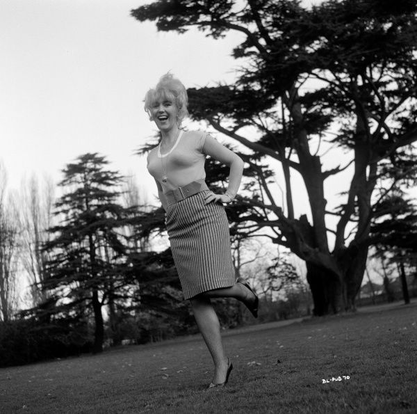 Gwendolyn Watts smiles in a photo taken in a garden (possibly Shepperton Studios) for the promotion of Billy Liar in 1963