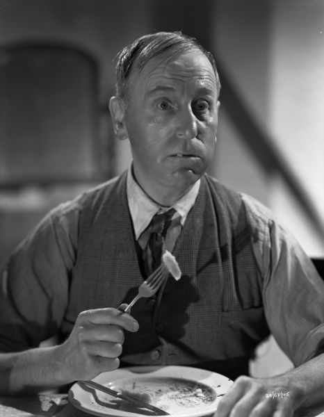 Wylie Watson in character as Spicer in the middle of a meal staged to promote the release of Brighton Rock in 1947