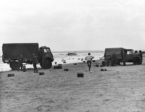 Two British Army trucks stranded on the beach