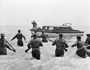 British soldiers run towards the boat of John Holden (Richard Attenborough)
