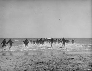 British soldiers run towards the small boats