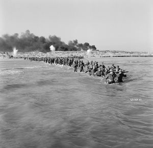 British troops walk into the water to try and board one of the small boats