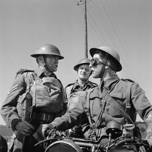 Corporal Bins (John Mills) asks information to another British soldier on a motorbike