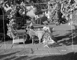 Edith, played by Valerie Hobson and Louis, played by Dennis Price take tea in the garden