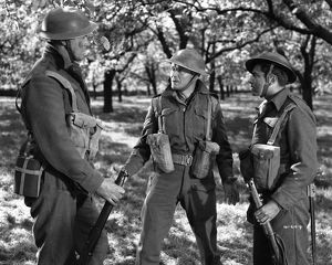 John Mills as Corporal Tubby Bins assesses the situation in the French countryside