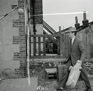 Charlie walks amongst damaged terraced houses
